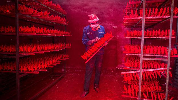 Man wearing a Christmas hat works at a factory producing Christmas decorations in Yiwu