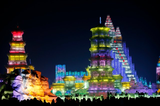 Visitors are silhouetted against lighted ice sculptures at the Harbin Ice and Snow Sculpture Festival in Harbin