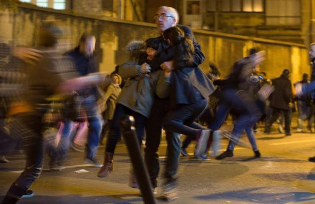 Čovek grli dva deteta u panici nastaloj tokom pomena žrtvama Pariskog napada u restoranu Le Petit Cambodge i hotelu Carillon, Pariz (15.nov)