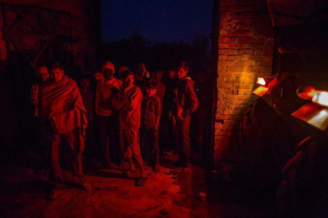 Noćno okupljanje meštana u kući prve glave sela, osvetljeno kočionim svetlom traktora, Fateh Nagla, Utar Pradeš, Indija, 14. januara (Prashanth Vishwanathan/Bloomberg)