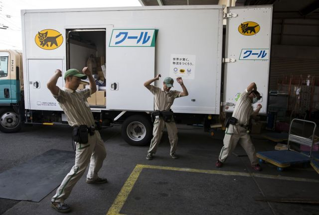 Vozaći kompanije Yamato Transport Co. pored kamiona za isporuku, Tokio, 30. maj (Tomohiro Ohsumi/Bloomberg)