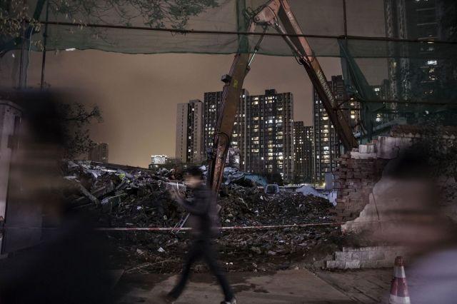 Pešaci prolaze kraj utovarivača u srušenom naselju, Čengdu, Kina, 10. april (Qilai Shen/Bloomberg)