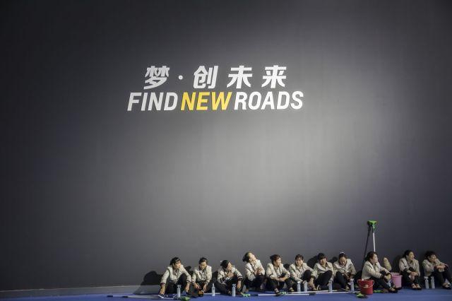 Čistači s mopovima i kofama sede ispod zidnih murala, Šangaj, 19. april (Qilai Shen/Bloomberg)