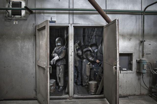 Radnici donose zaštitnu odeću pre nego što uđu u komoru za peskiranje u fabrici u Kidongu, Kina, 22. jun (Qilai Shen/Bloomberg)