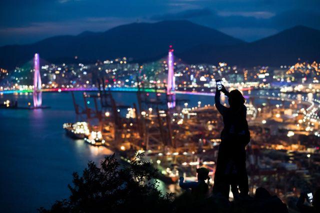 Žena fotografiše luku Busan pametnim telefonom, Južna Koreja, 16. jul (SeongJoon Cho/Bloomberg)