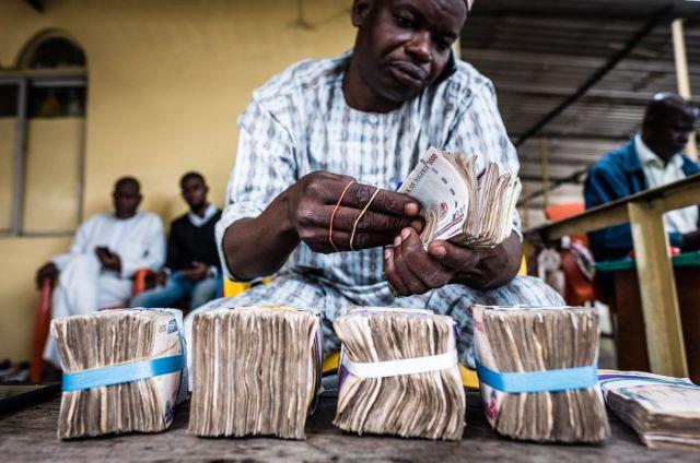 Diler devizama broji pakete papirnih novčanica naira u Lagosu, Nigerija, 26. jul (Tom Saater/Bloomberg)