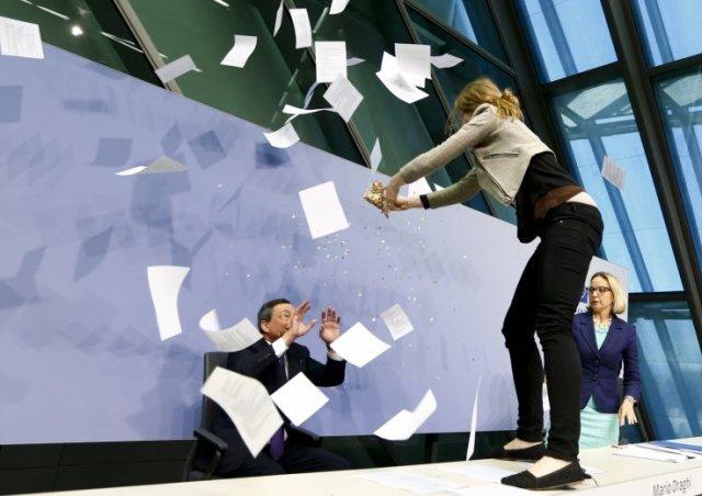 """Aktivistkinja Femen-a na stolu iznad Marija Dragija tokom konferencije za štampu 15 aprila 2015, protestuje zbog """"diktatorskog tretmana ECB-a prema Grčkoj i drugim zaduženim zemljama EU (Foto: Fortune)"""