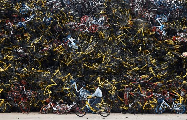 """01. Radnik vozi pokraj """"groblja"""" unajmljenih bicikala - ogromne gomile neiskorišćenih dvotočkaša na utrini u Sijamenu, provincija Fuđijan (Kina, 13. decembra 2017. godine)"""