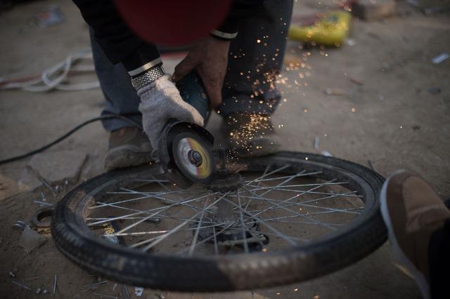 13. Radnik zaposlen na popravci šering bicikala u centru za popravku (Peking, 6. apr 2017, Nicolas Asfouri/ AFP/ Getty)