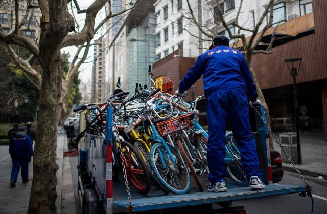 20. Radnik jedne šangajske parking-firme stavlja na kamion napuštene šering-bicikle, doskora u vlasništvu servisa Mobike i Ofo (20. feb 2017, Johannes Eisele/ AFP/ Getty)