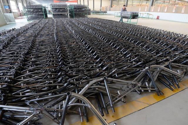 21. Kineski radnik premešta ramove novih šering-bicikala u vlasništvu servisa Ofo, u fabrici bicikla u Handanu, provincija Hebei na severu Kine (13. apr 2017, AFP/ Getty)