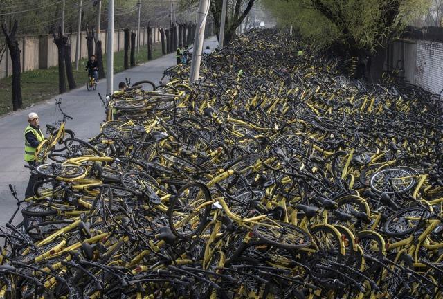 """26. Radnik šering-bajk kompanije Ofo stavlja oštećeni bicikl na gomilu pokraj improvizovanog servisa za popravku. Hiljade napuštenih bicikala leži po skladištima širom Pekinga, nakon što su """"penzionisani"""" 29. marta 2017 (Kevin Frayer/ Getty)"""